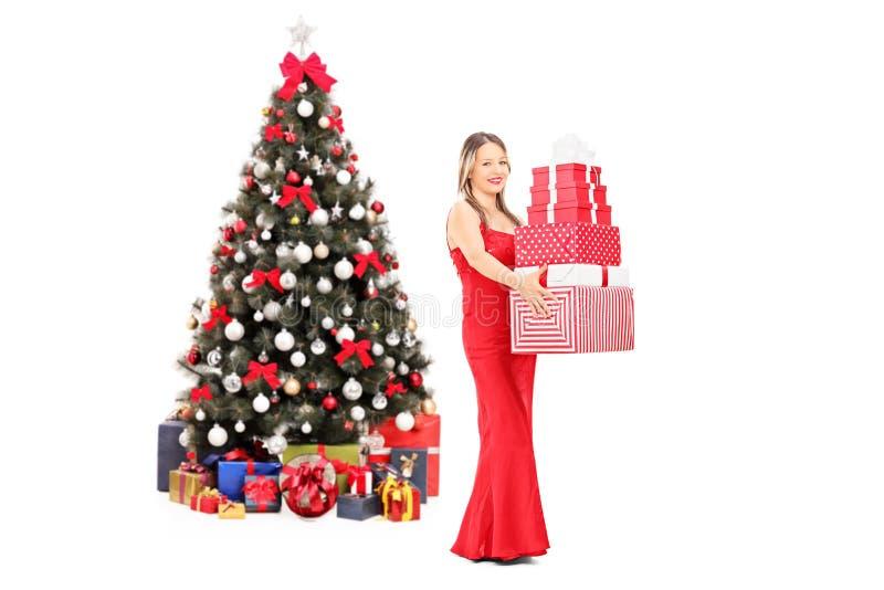 女孩在圣诞树前面的藏品礼物 免版税库存照片