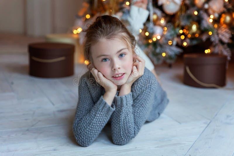 女孩在圣诞树附近说谎 免版税图库摄影