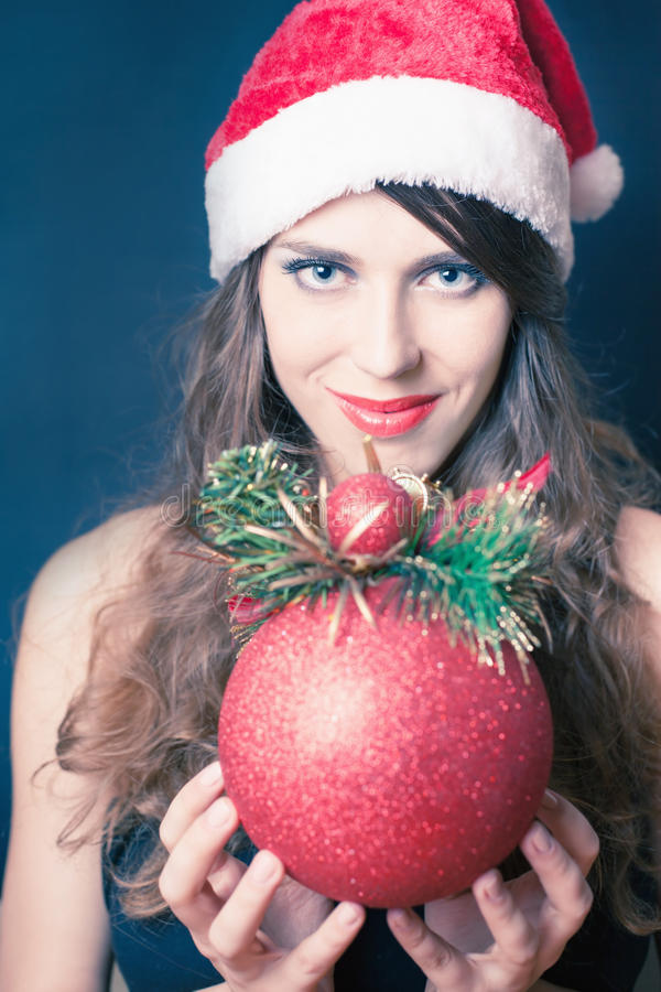 女孩在圣诞老人帽子穿戴了,拿着圣诞节装饰 免版税库存照片