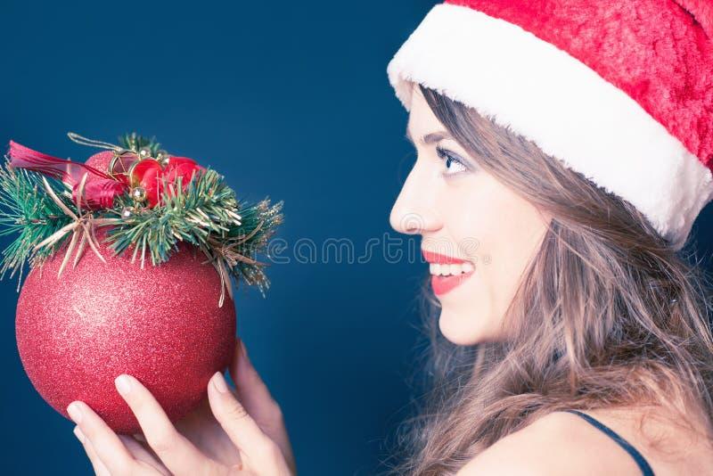 女孩在圣诞老人帽子穿戴了,拿着圣诞节装饰 库存照片