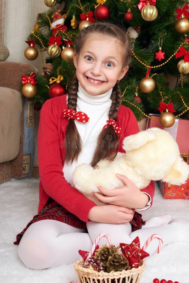 女孩在圣诞节杉树和在家使用坐与熊,圣诞节装饰附近,愉快的情感,寒假概念 免版税库存照片