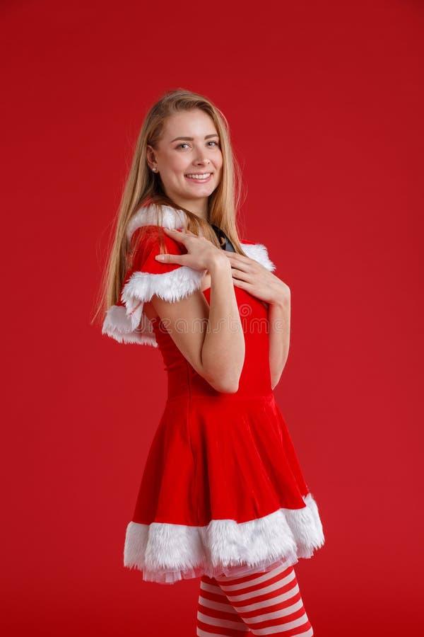 女孩在圣诞节礼服,站立斜向一边和微笑穿戴了逗人喜爱 在一个红色背景 库存图片