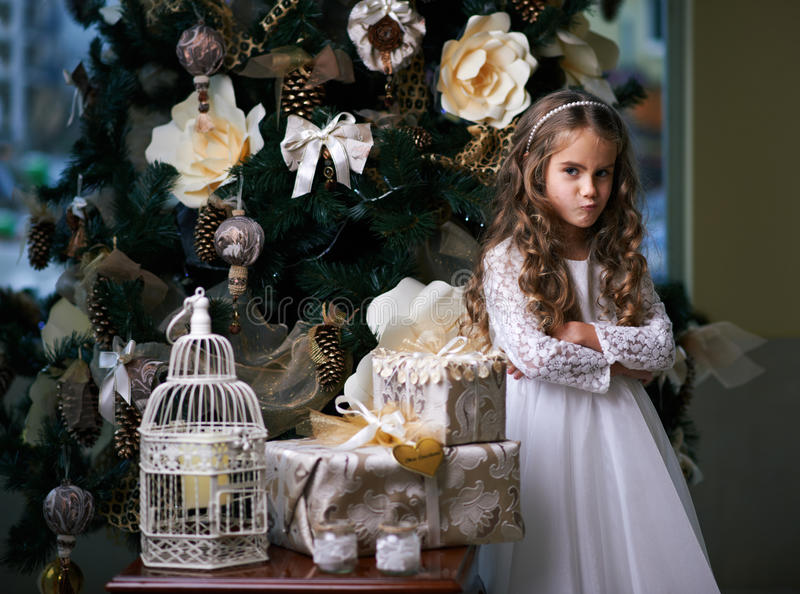 女孩在圣诞节礼物附近做鬼脸 图库摄影