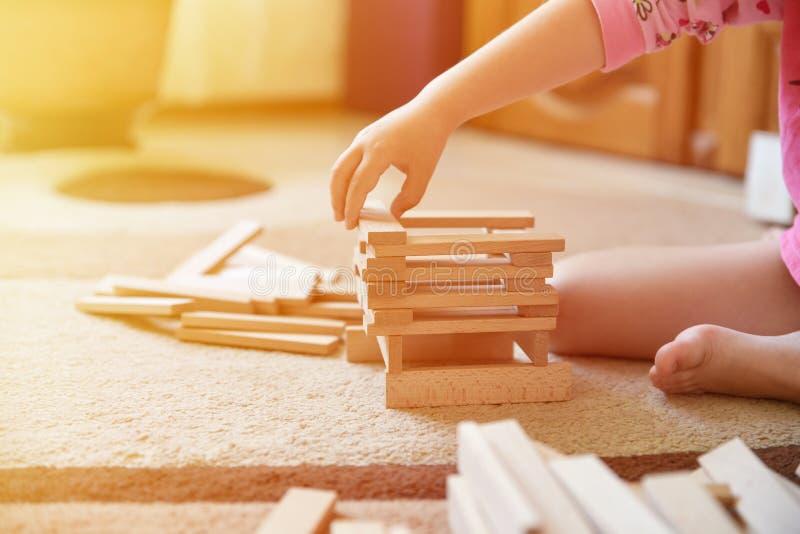 女孩在地毯的戏剧比赛和修造耸立,发展玩具,光线影响 免版税库存照片