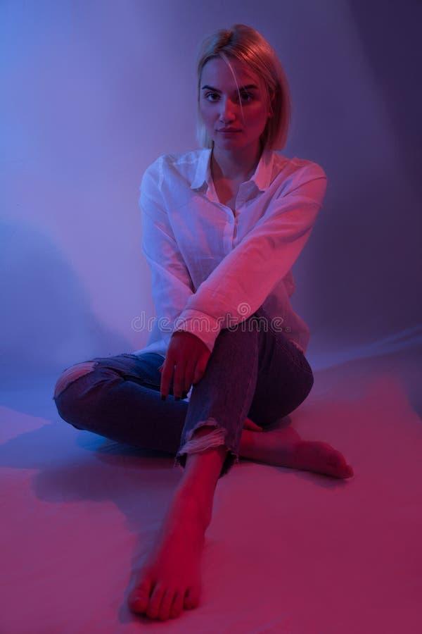 女孩在坐下在有五颜六色的蓝色和红灯的演播室的蓝色牛仔裤和赤脚 免版税库存照片