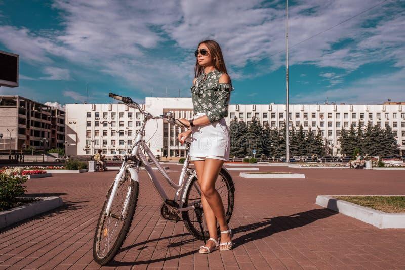 女孩在夏天在城市,在一辆白色自行车旁边站立,在一条白色裙子和一件绿色女衬衫 明亮的好日子 库存照片