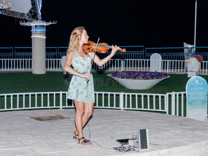 女孩在夏天晚上为小提琴的路人使用在纳哈里亚,以色列江边  免版税图库摄影