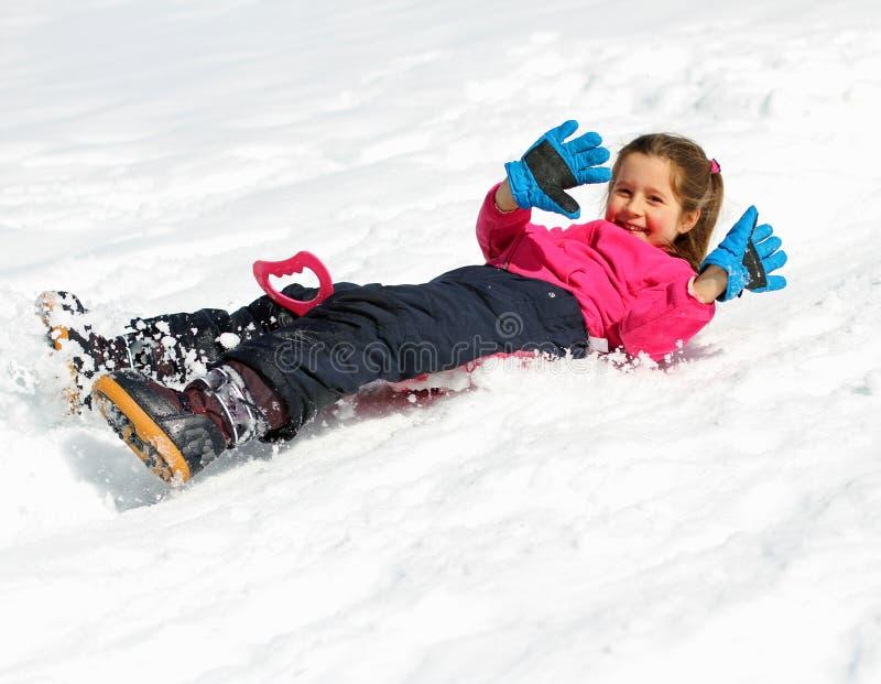 女孩在多雪的山滑倒下来 库存图片