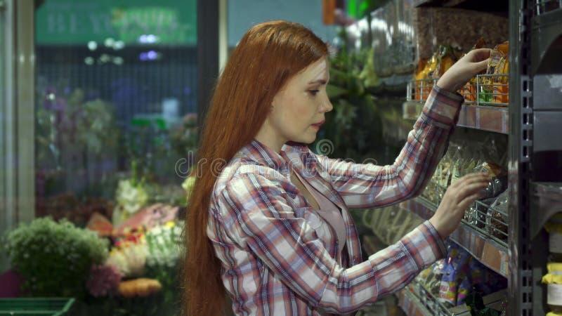 女孩在大型超级市场选择坚果 图库摄影