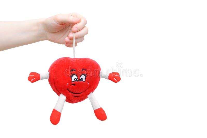 女孩在她的手上拿着一个软的玩具以心脏的形式 免版税图库摄影
