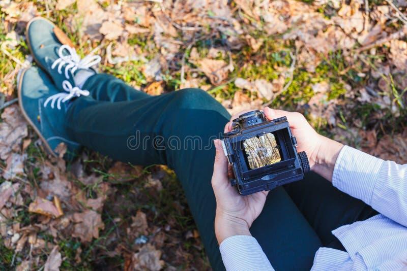 女孩在她的手上拿着一台老影片照片照相机在春天森林 免版税库存图片