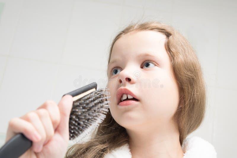 女孩在她的手上拿着一把梳子,象话筒并且在卫生间里唱歌 免版税库存照片