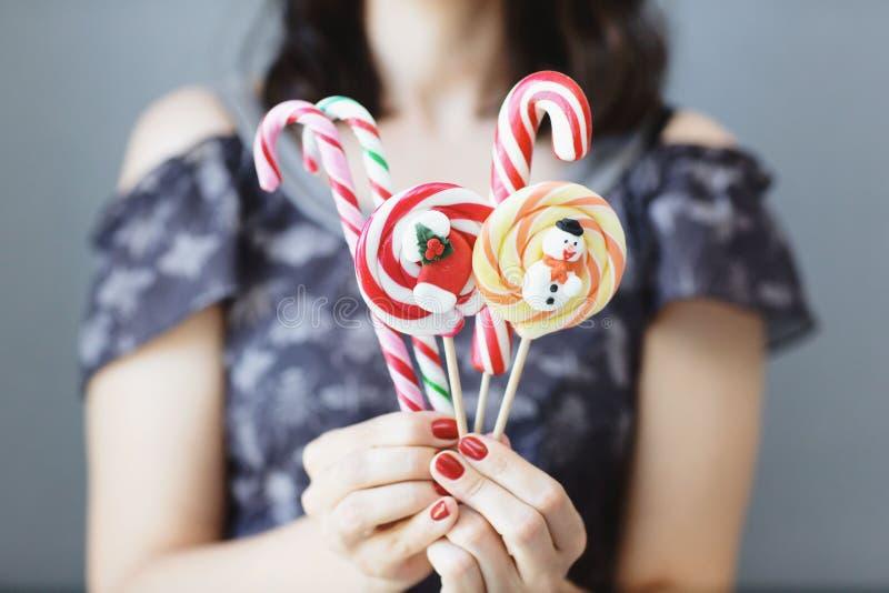 女孩在她的手上拿着色的圣诞节糖果 在前景的甜点 o 库存图片