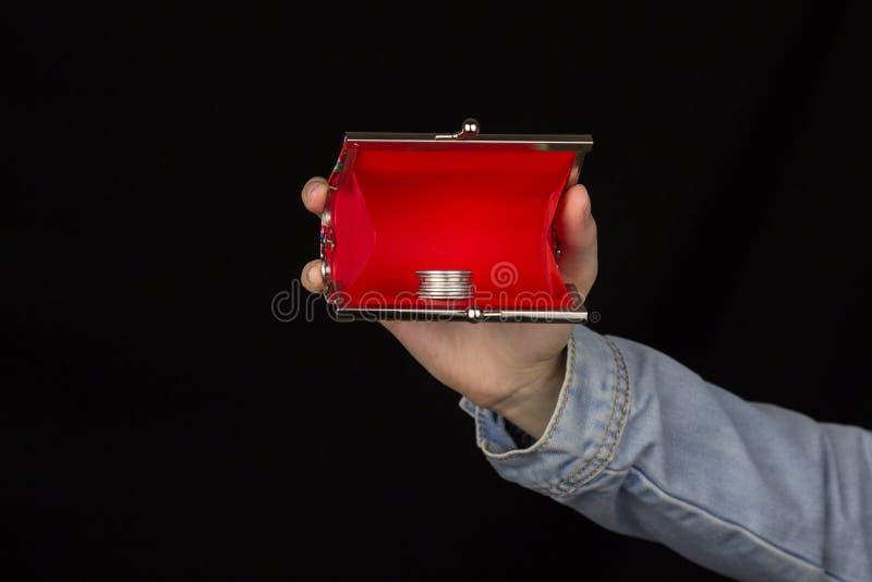 女孩在她的手,硬币,黑背景,特写镜头财务上的拿着一个红色钱包 免版税图库摄影