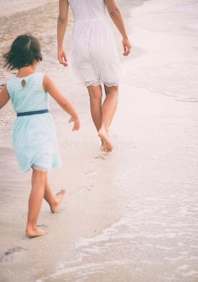 女孩在她的母亲脚步设法走  库存照片