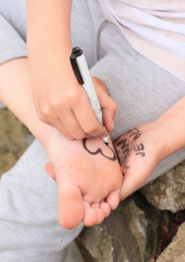 女孩在她的脚底的图画心脏 免版税库存图片