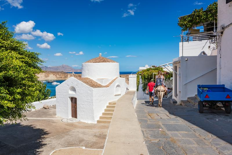 女孩在她的途中的骑马驴对Lindos罗得岛,希腊上城  免版税库存照片