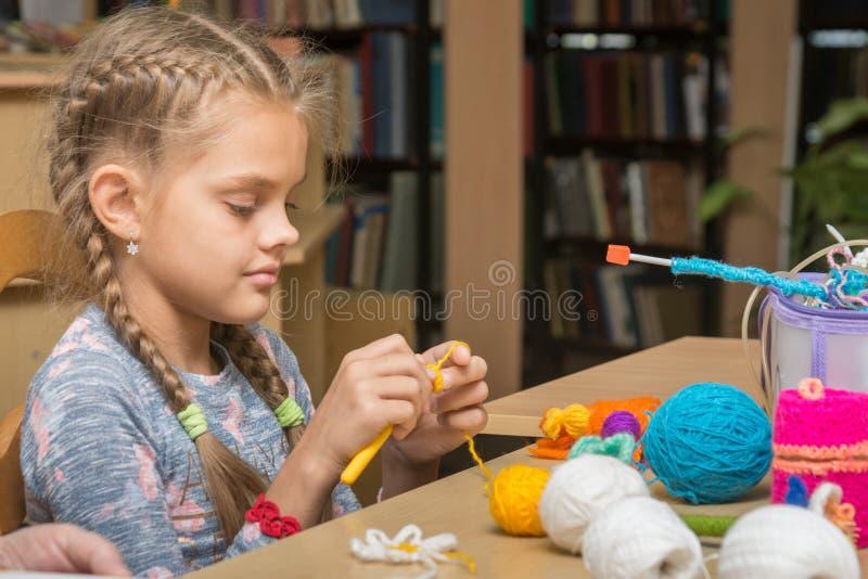 女孩在学校图书馆中编织刺绣 免版税库存照片