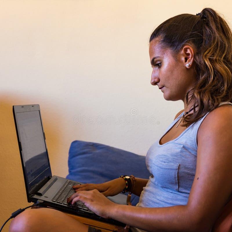 女孩在家做在长沙发的家庭作业有膝上型计算机的 免版税库存图片