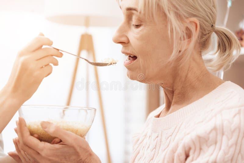 女孩在家护理年长妇女 女孩帮助有晚餐的妇女 免版税库存照片