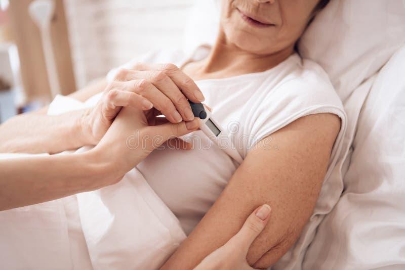 女孩在家护理年长妇女 女孩检查温度与电子温度计 免版税库存图片