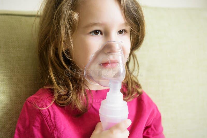 女孩在家拿着吸入器面具或雾化器 免版税库存照片