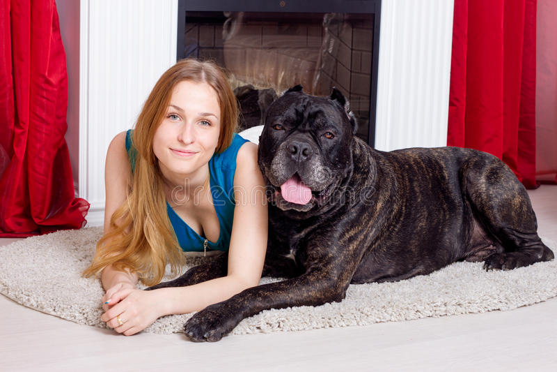 女孩在家是在与他的狗藤茎Corso的壁炉旁边 库存照片