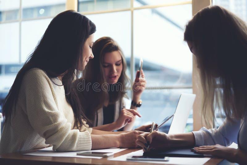女孩在对塑造使用wifi的网的咖啡馆使用便携式计算机和申请的名牌服装 免版税库存照片