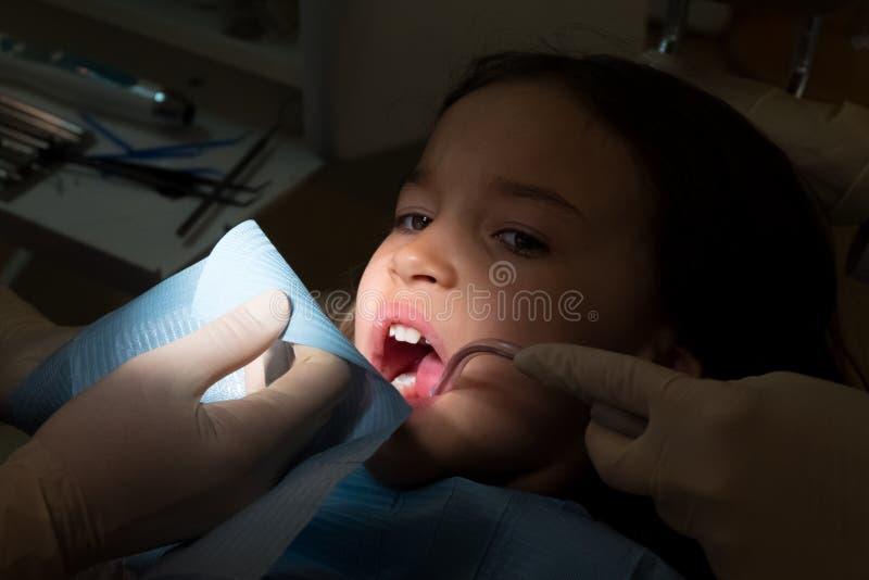 女孩在小儿科牙医办公室,乳齿的治疗 免版税库存照片