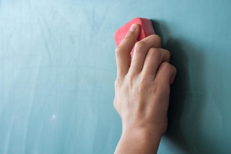 女孩在小学有海绵的清洁委员会递 免版税库存图片
