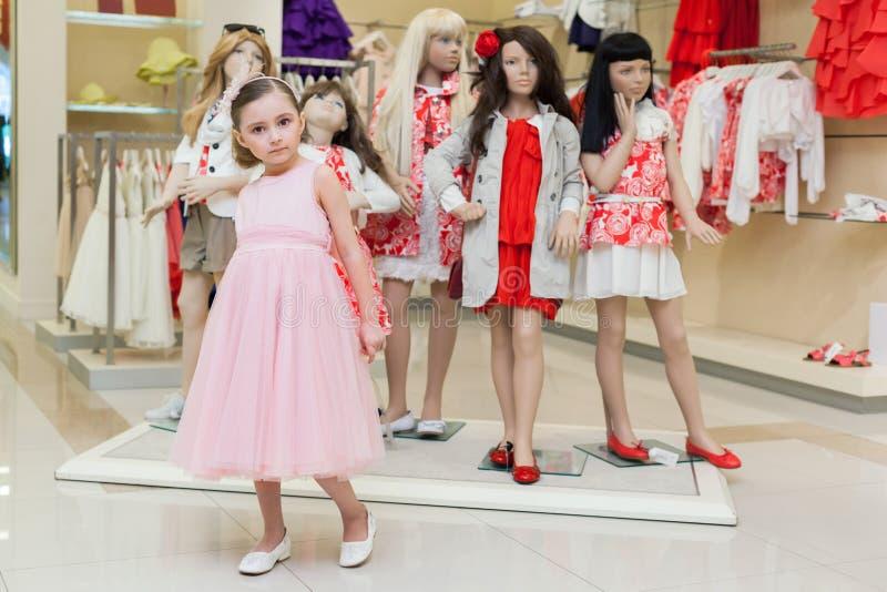 女孩在尝试在礼服的商店 库存照片