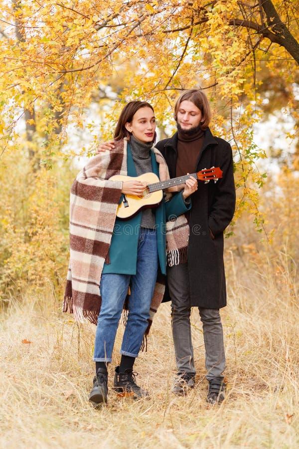 女孩在尤克里里琴使用在有长的头发的一个人旁边在秋天背景 免版税库存图片