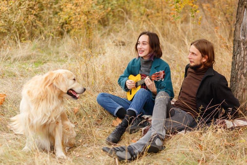 女孩在尤克里里琴播放对坐在一个人旁边的人在秋天森林里 图库摄影