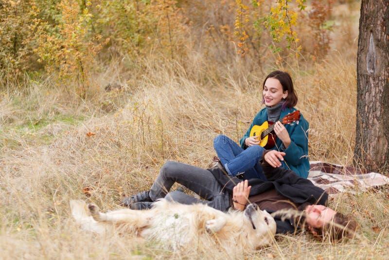 女孩在尤克里里琴演奏一个人和一条狗在秋天森林里 免版税库存图片