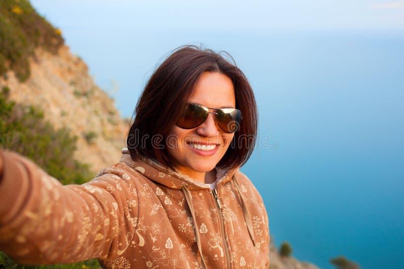女孩在山上面的射击selfie在海背景  免版税图库摄影