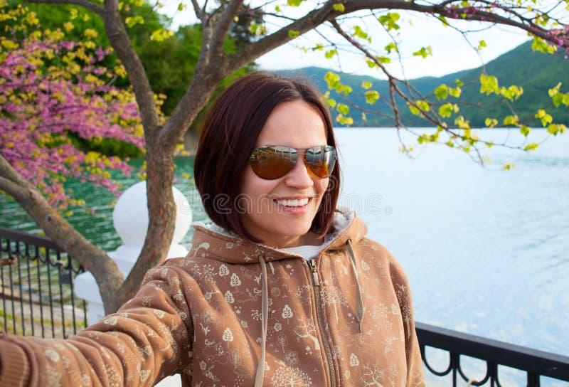 女孩在山和湖背景的射击selfie 免版税库存图片