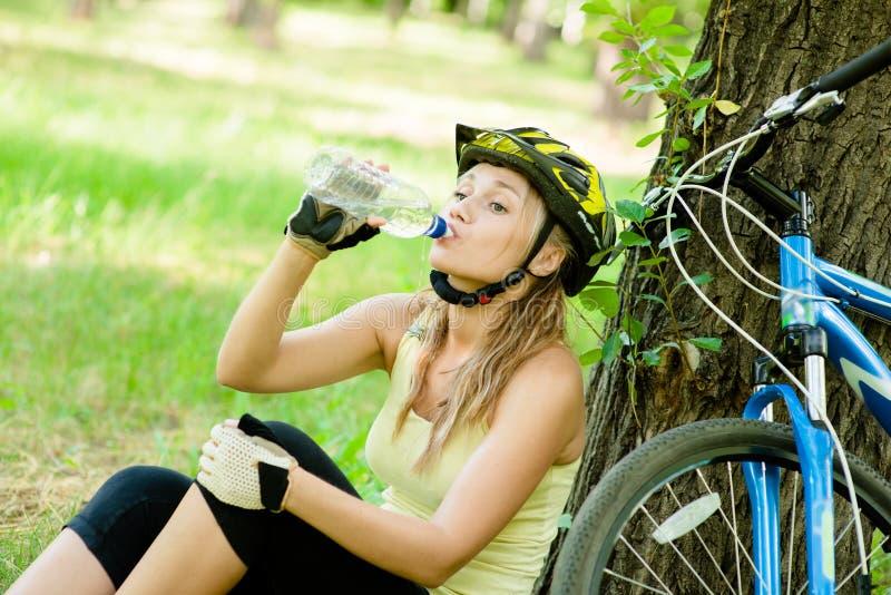 女孩在山骑自行车以后喝从瓶的水 库存照片