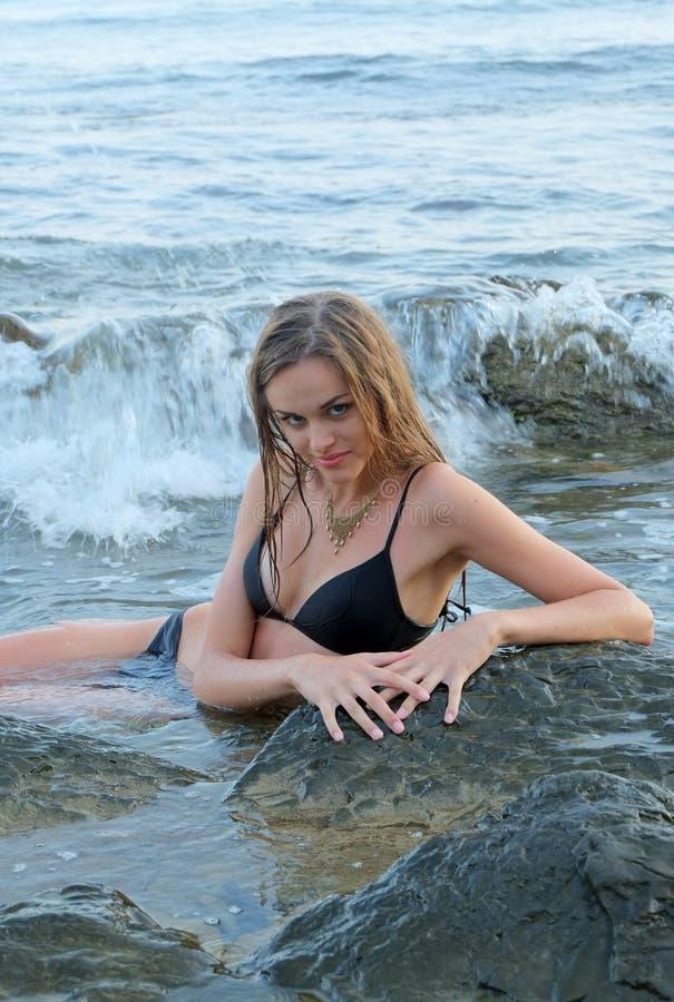 女孩在岩石旁边的海 免版税库存图片