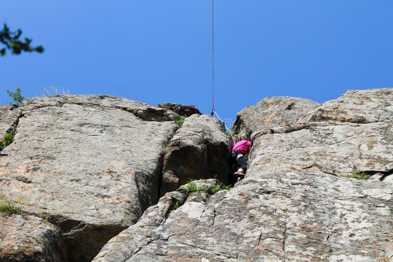 女孩在岩石的攀岩运动员攀登 免版税库存图片