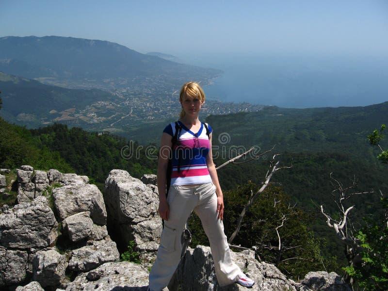 女孩在岩石站立反对背景 免版税库存照片