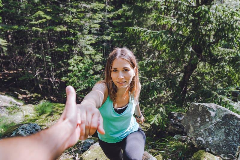 女孩在岩石,伙伴上升拔出协助的手 免版税库存照片
