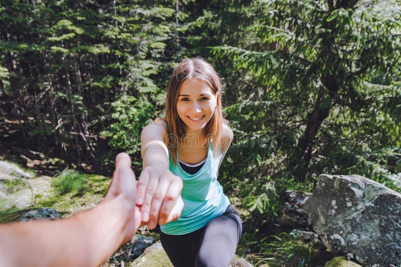 女孩在岩石,伙伴上升拔出协助的手 图库摄影
