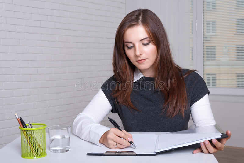 女孩在工作站在本文文件夹坐写 库存照片