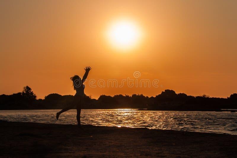 女孩在希腊的克利特感到快乐并且跳舞在Elafonisi海滩  图库摄影