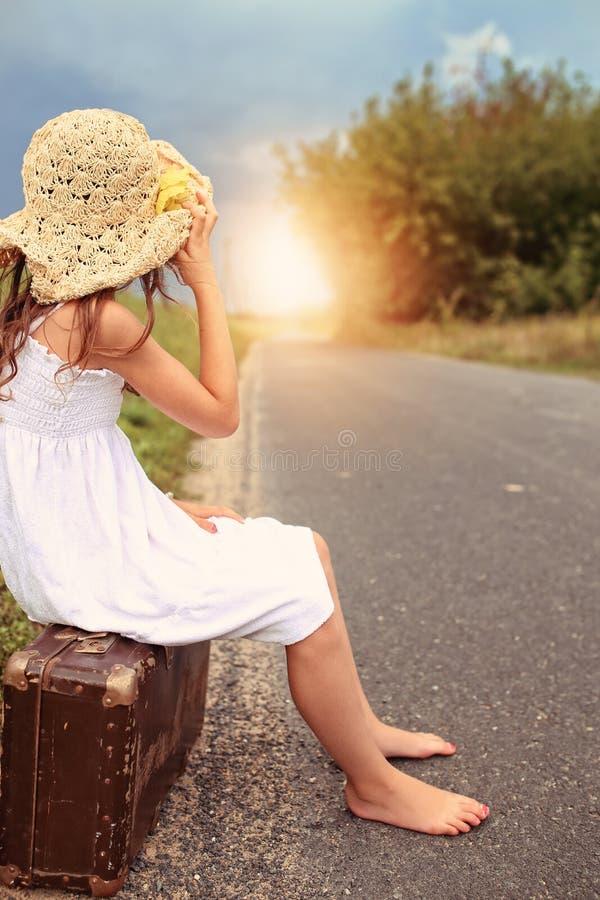 女孩在帽子坐手提箱 免版税库存照片