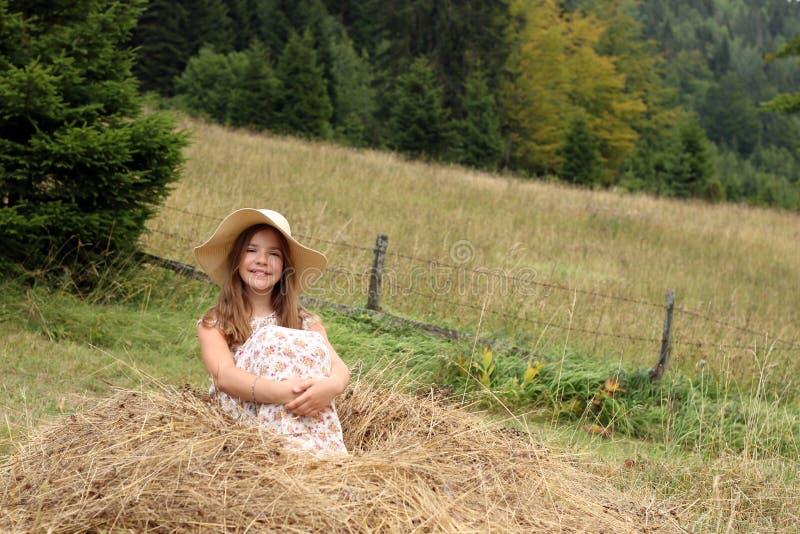 女孩在干草坐 图库摄影