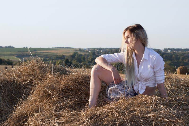 女孩在干草堆坐农村风景的背景 免版税库存图片
