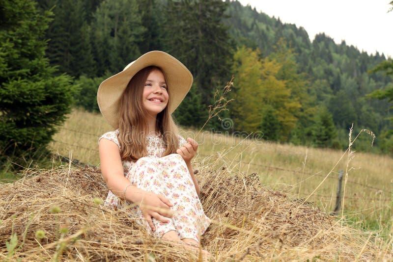 女孩在干草夏季坐 免版税库存图片