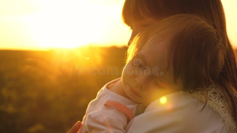 女孩在年轻妈妈的胳膊睡觉日落金黄光芒的  慢的行动 免版税库存照片
