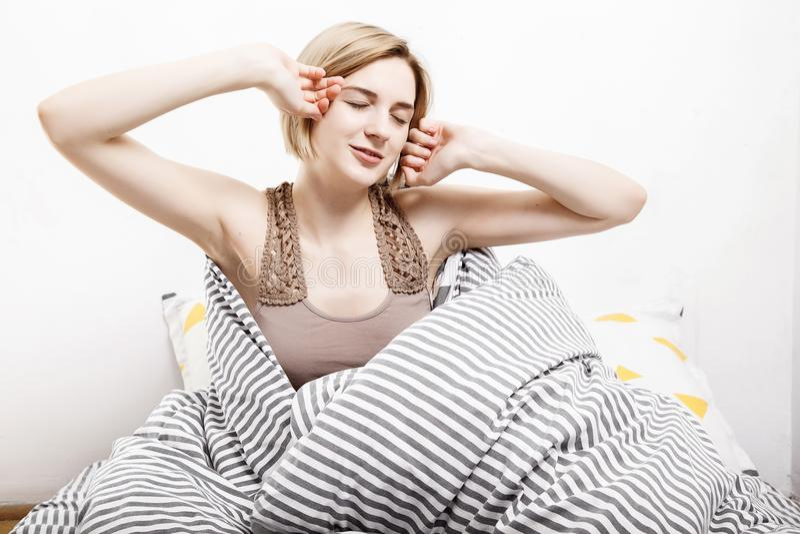 女孩在床上喝咖啡 女孩早晨叫醒的早晨女孩 休眠 唤醒早晨 写入新闻 免版税库存图片